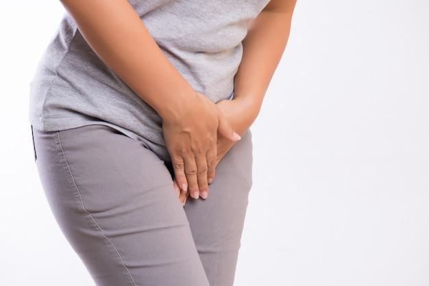 Frauenhände, die ihren unteren bauch der gabelung drücken. medizinisches oder gynäkologisches problem