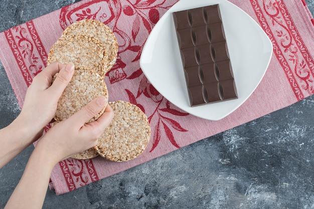 Frauenhände, die knuspriges reisbrot mit tafel schokolade halten.