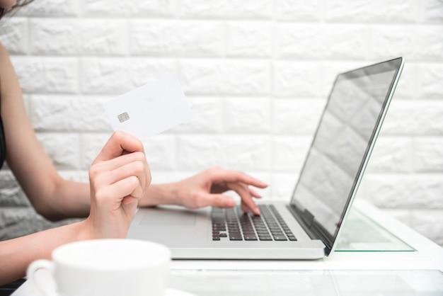 Frauenhände, die kreditkarte für on-line-einkaufen halten oder produkt vom internet bestellen, wenn sie laptop verwenden