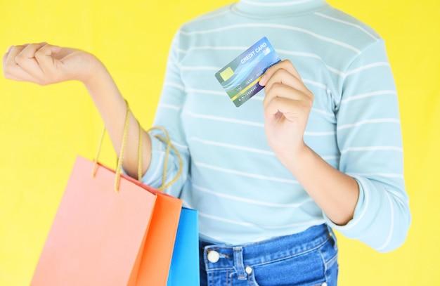 Frauenhände, die kreditkarte halten und einkaufstasche auf gelbem hintergrund halten.