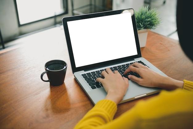Frauenhände, die laptop-computer mit leerem bildschirm für schein herauf schablonenhintergrund schreiben