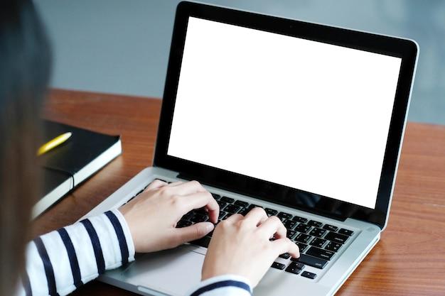 Frauenhände, die laptop-computer mit leerem bildschirm für spott oben beim sitzen im café schreiben