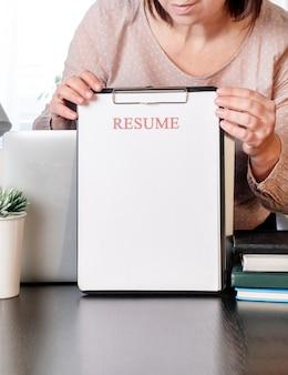 Frauenhände, die lebenslaufanwendung nahe ihrem arbeitsplatz mit laptop halten.