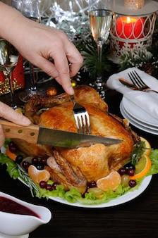 Frauenhände, die leckeres saftiges würziges appetitliches gebratenes ganzes huhn aufschneiden