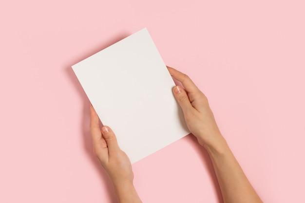 Frauenhände, die leere karte auf rosa tisch halten