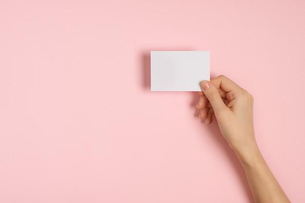 Frauenhände, die leere visitenkarte auf rosa tisch halten