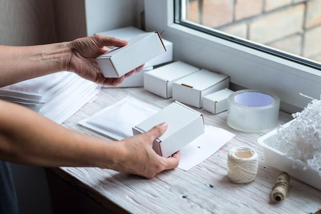 Frauenhände, die mit kartonschachtel und papierpostumschlag arbeiten