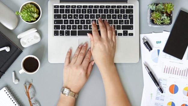 Frauenhände, die mit laptop auf einer grauen büroschreibtisch-draufsicht tippen. geschäftskonzept