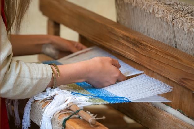 Frauenhände, die muster auf webstuhl weben.