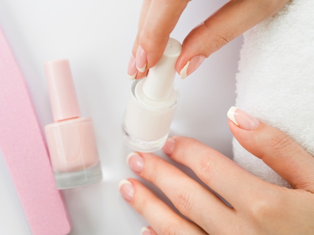 Frauenhände, die nagellack halten