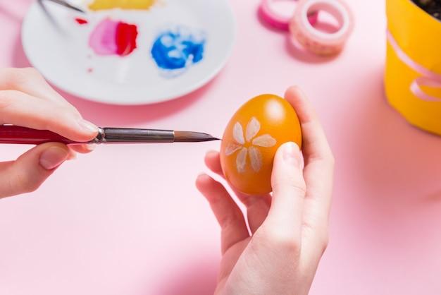 Frauenhände, die ostereier auf rosa schreibtisch malen