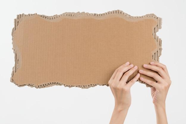 Frauenhände, die pappe mit dem exemplarplatz getrennt auf weiß anhalten
