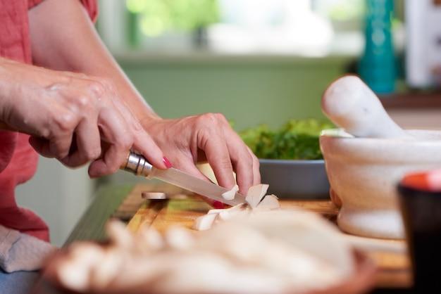 Frauenhände, die pilze schneiden