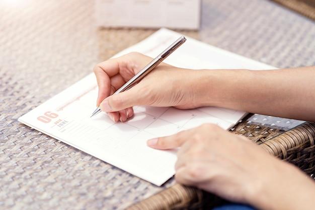 Frauenhände, die plan auf notizbuch schreiben, tagesordnung und zeitplan unter verwendung des kalenders planen