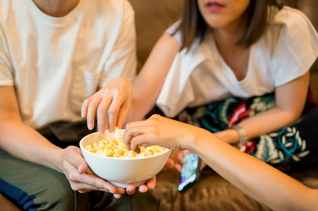 Frauenhände, die popcorn vom aufpassenden film der schüssel mit freund nehmen.