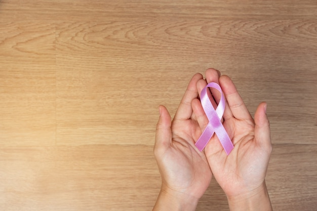 Frauenhände, die rosa bogen, rosa bänder, auf hölzernem hintergrund halten