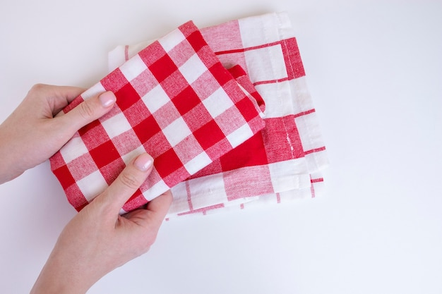 Frauenhände, die rot karierte küchentücher halten