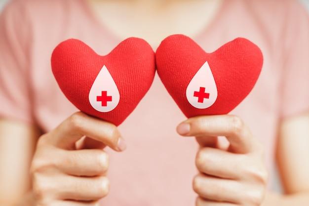 Frauenhände, die rotes herz mit blutspenderzeichen halten gesundheits-, medizin- und blutspendekonzept