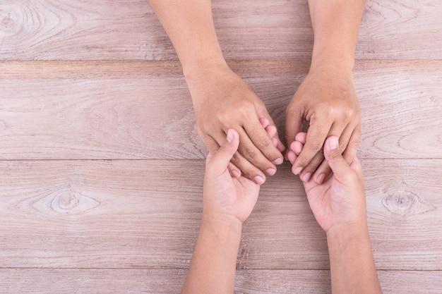 Frauenhände, die rotes herz und stethoskop halten