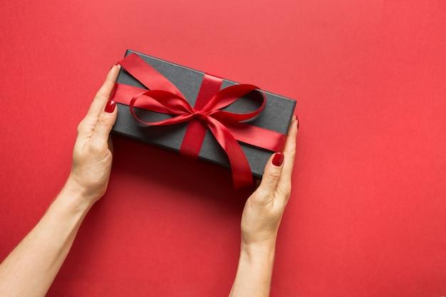 Frauenhände, die schwarze geschenkbox halten, gewickelt mit rotem band auf roter oberfläche. valentinstagskarte.