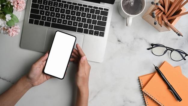 Frauenhände, die smartphone des leeren bildschirms auf büromarmorarbeitsplatz halten
