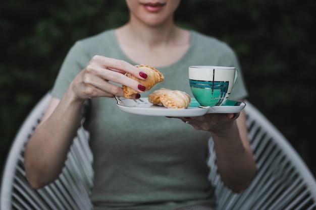 Frauenhände, die snack mit kaffeetasse halten, die im garten zu hause sitzt.