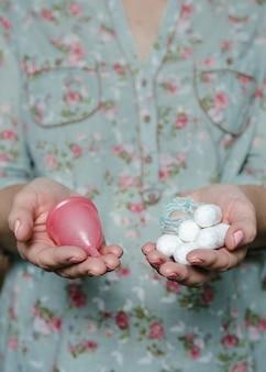 Frauenhände, die tampons und menstruationstasse halten vergleich verschiedener methoden der weiblichen intimhygiene.
