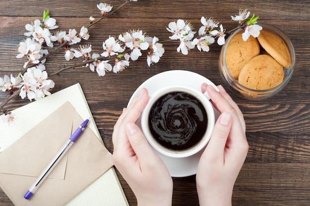 Frauenhände, die tasse kaffee auf hölzernem hintergrund halten