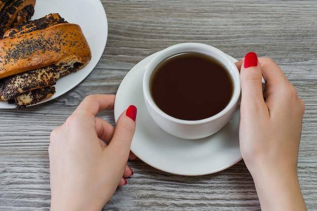Frauenhände, die tasse tee über untertassenbrötchen auf hölzernem tischhintergrund der platte halten