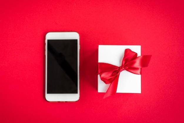 Frauenhände, die telefon auf rot mit weihnachtsdekorationen und geschenken halten.