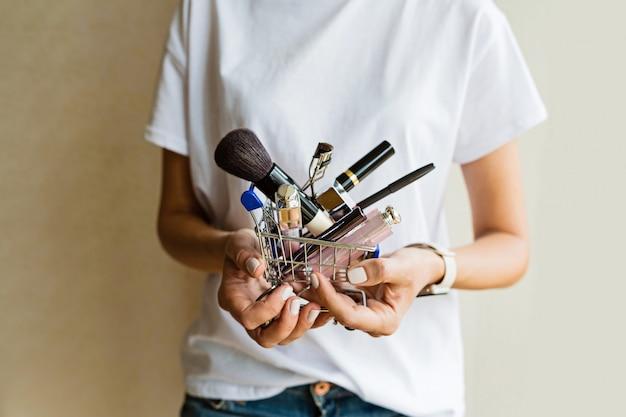 Frauenhände, die wagen mit make-up-produkten halten