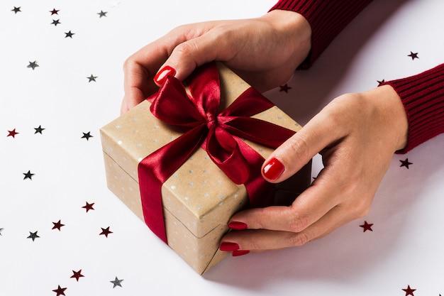 Frauenhände, die weihnachtsferiengeschenkbox auf verzierter festlicher tabelle halten