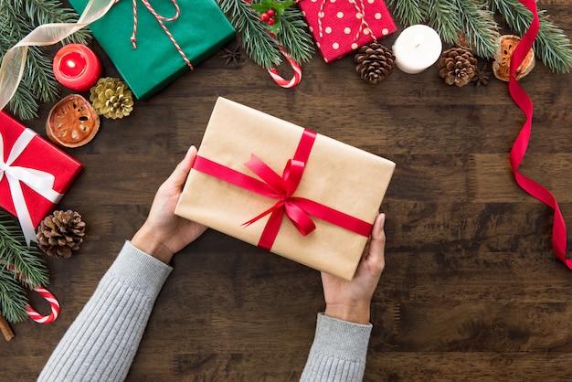 Frauenhände, die weihnachtsgeschenk auf hölzerner tabelle zeigen