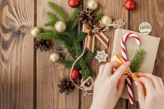 Frauenhände, die weihnachtsgeschenk einwickeln, schließen oben. unvorbereitete weihnachtsgeschenke auf holz. draufsicht