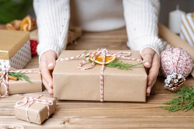 Frauenhände, die weihnachtsgeschenk einwickeln