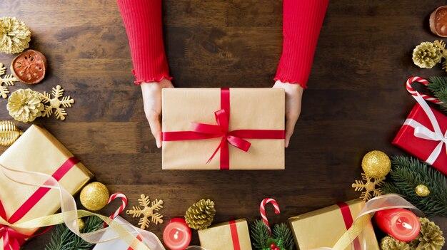 Frauenhände, die weihnachtsgeschenk geben
