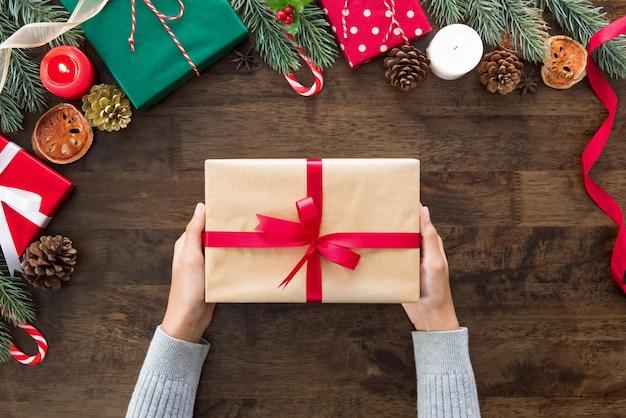 Frauenhände, die weihnachtsgeschenkbox auf hölzerner tabelle zeigen