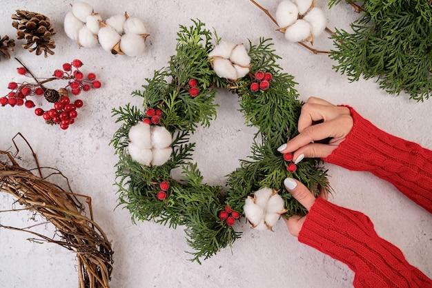 Frauenhände, die weihnachtskranzhandwerk auf hölzerner draufsicht machen
