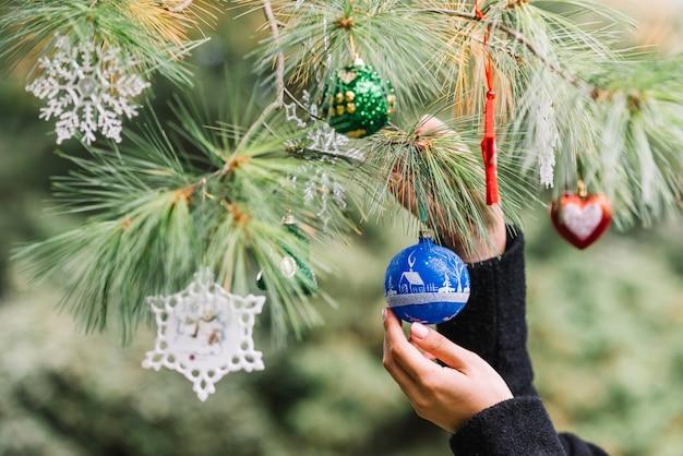 Frauenhände, die weihnachtsspielwaren auf zweig im wald hängen