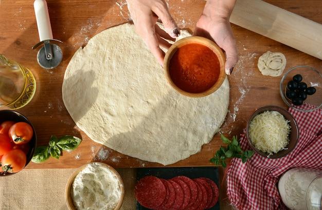 Frauenhände, die zu hause pizza kochen und alle bestandteile hinzufügen