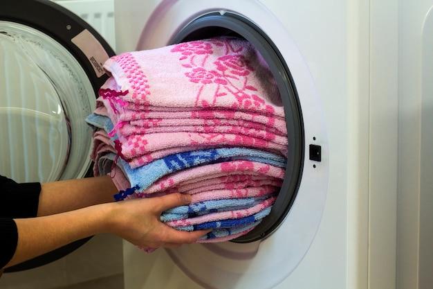 Frauenhände, die zu hause wäscherei in waschmaschine setzen