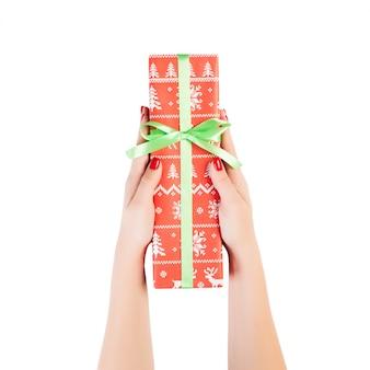 Frauenhände geben das weihnachtshandgemachte lokalisierte geschenk