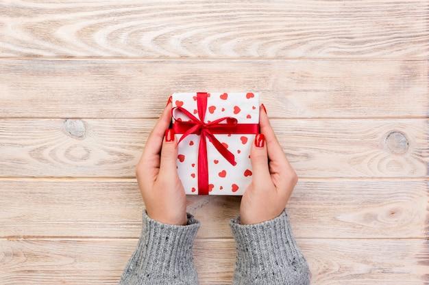Frauenhände geben draufsicht der anwesenden geschenkbox
