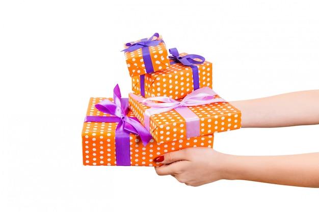 Frauenhände geben eingewickelten satz handgemachtes geschenk des weihnachten oder anderen feiertags im orange papier mit purpurrotem band.