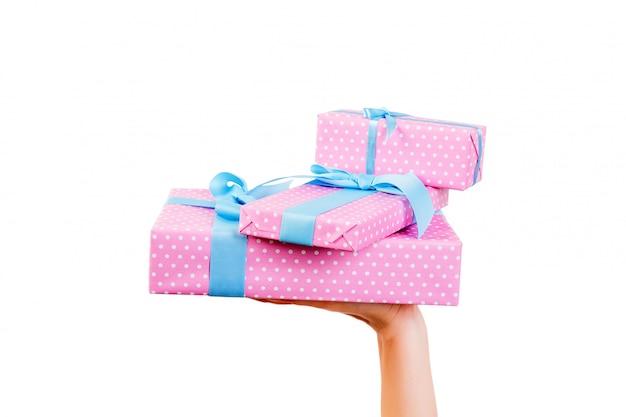 Frauenhände geben eingewickelten satz weihnachten oder anderes handgemachtes geschenk des feiertags im rosa papier mit blauem band