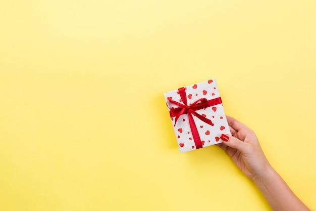 Frauenhände geben eingewickelten valentinsgruß im papier mit rotem band.