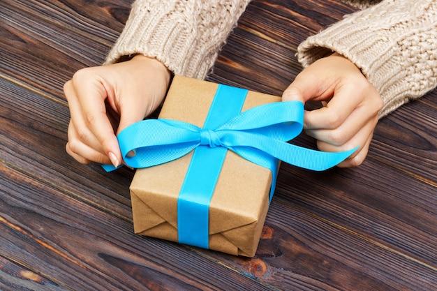 Frauenhände geben eingewickelten valentinsgruß oder anderes handgemachtes geschenk des feiertags im papier mit blauem band.