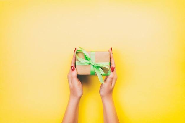 Frauenhände geben eingewickelten valentinsgruß oder anderes handgemachtes geschenk des feiertags im papier mit habsuchtband.