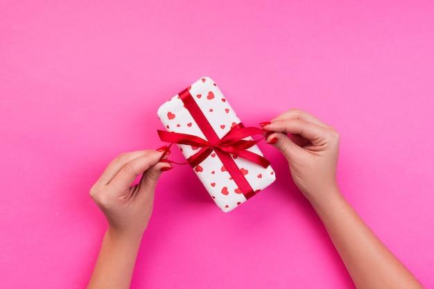 Frauenhände geben eingewickelten valentinsgruß oder anderes handgemachtes geschenk des feiertags im papier mit rotem band. präsentkarton, rote herzdekoration des geschenks auf rosa tabelle, draufsicht mit kopienraum für sie entwerfen