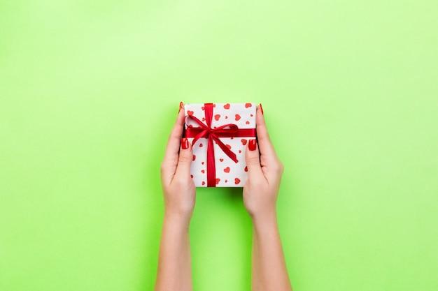Frauenhände geben eingewickelten valentinsgruß oder anderes handgemachtes geschenk des feiertags im papier mit rotem band.